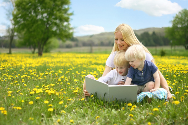 Mom reading a book with her child on the grass Stock Photo