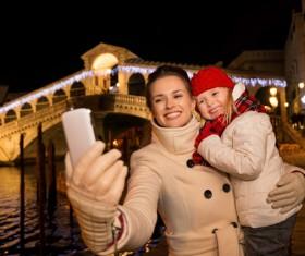 Mother holding children using smartphone selfie Stock Photo