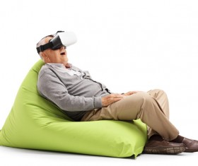 Senior man sitting in inflatable chair looking VR Stock Photo