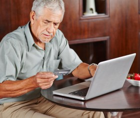 Senior man using laptop for online payment Stock Photo