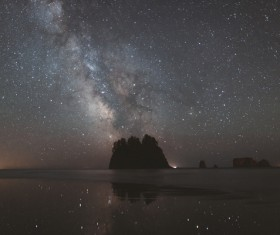 Sparkling starry sky above calm sea Stock Photo
