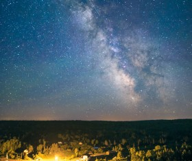 Sparkling starry sky above forest Stock Photo