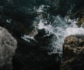 Splashing wave on rocks in sea Stock Photo