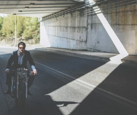 Stylish man riding motorbike on empty road Stock Photo