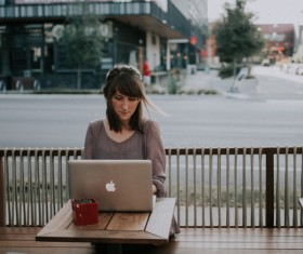 Using laptop woman in the street open-air cafe Stock Photo