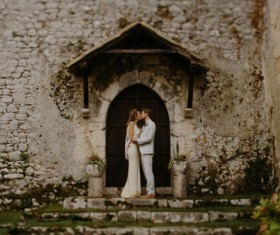 Wedding couple kissing in front of vintage building Stock Photo