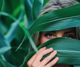Woman Hide face by corn leaf Stock Photo