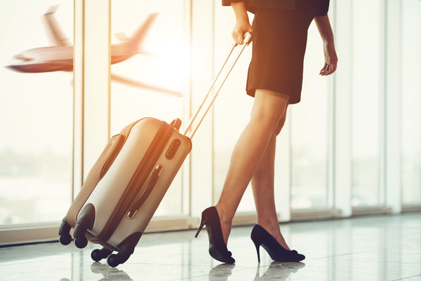 Woman at the airport with suitcase Stock Photo
