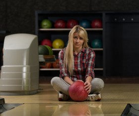 Woman holding a bowling ball sitting on the floor Stock Photo 01