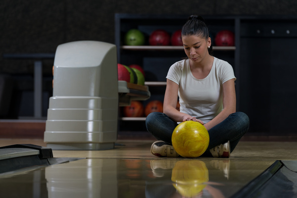 Woman holding a bowling ball sitting on the floor Stock Photo 02