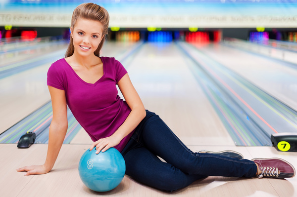 Woman holding a bowling ball sitting on the floor Stock Photo 03