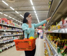 Woman in supermarket buying food calls Stock Photo 01