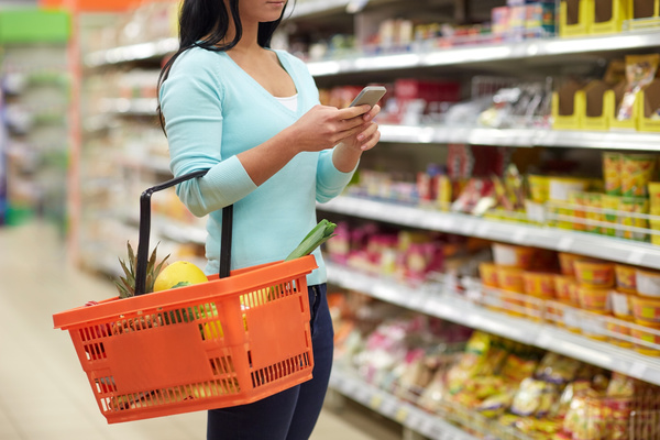 Woman in supermarket buying food looking at mobile phone Stock Photo