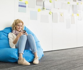Woman playing smart phone while sitting in inflatable chair Stock Photo