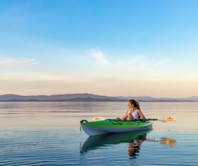 Woman rowing on calm river Stock Photo