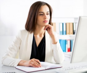 Woman sitting at computer and recording information Stock Photo