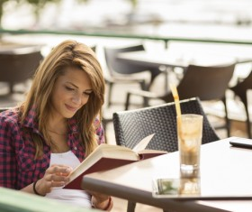 Woman sitting at open-air cafe reading a book Stock Photo