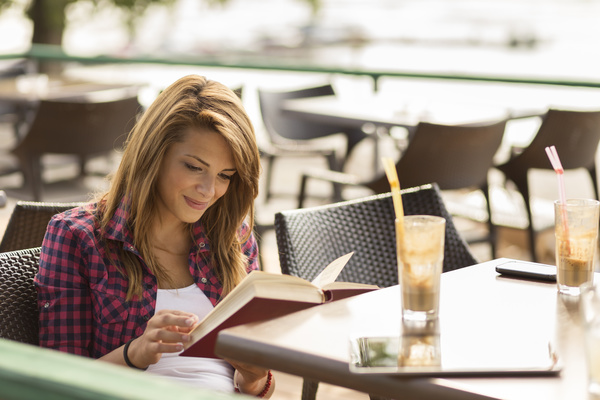 Woman sitting at open air cafe reading a book Stock Photo