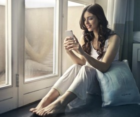 Woman sitting at the window looking at cell phone Stock Photo