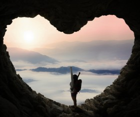 Woman standing in heart shaped cave mouth Stock Photo