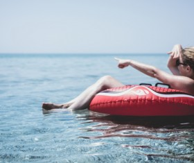 Young girl joyful on buoy on beach Stock Photo