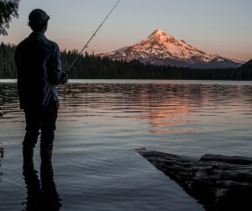 man fishing on calm lake Stock Photo