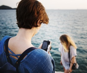 woman taking photograph on sea scene Stock Photo