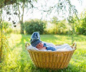 A baby sleeping in a wicker basket Stock Photo (1)