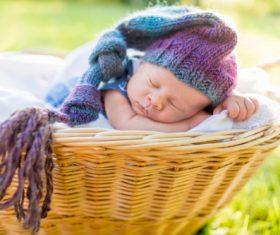 A baby sleeping in a wicker basket Stock Photo (4)