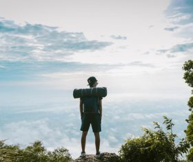 Backpacker standing on top of mountain enjoys high altitude scenery Stock Photo