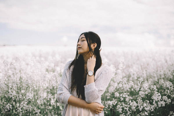 Beautiful asian woman posing on flowers field Stock Photo