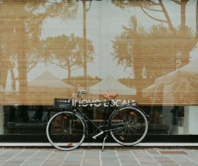 Bicycle leaning outside of glass door house Stock Photo