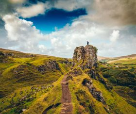 Clouds above green wide highland scenery Stock Photo