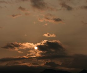Clouds and sun above mountain range at dusk Stock Photo