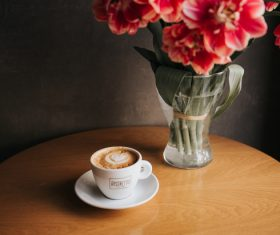 Coffee cup and decorative flowers on table Stock Photo
