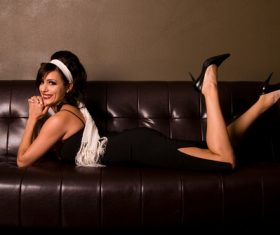 Confident smiling woman lying on the couch Stock Photo