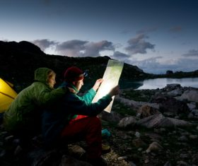 Couple looking at map outside camping tent Stock Photo