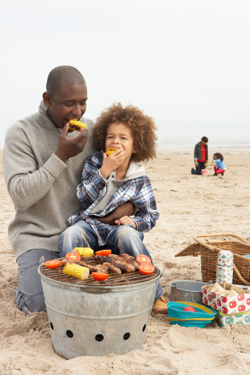 Father and daughter eating barbecue corn Stock Photo