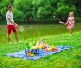 Father and daughter playing tennis and picnic food Stock Photo
