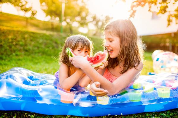 Feeding sister to eat watermelon Stock Photo