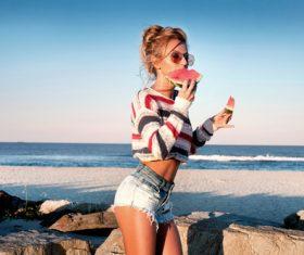 Girl eating watermelon while walking Stock Photo