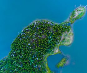 Green island on blue sea from high view Stock Photo