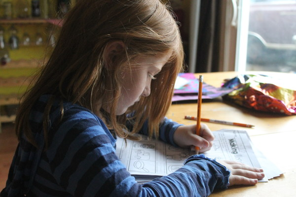 Little girl writing homework seriously Stock Photo