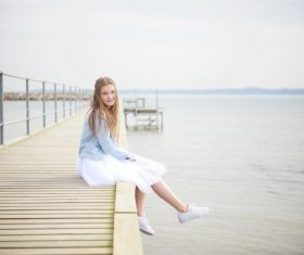 Maiden sitting on wooden bridge Stock Photo