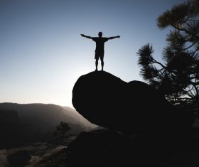 Man posing on big stone at dusk Stock Photo