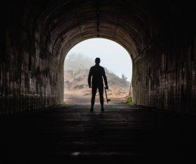 Man standing alone in dark tunnel Stock Photo