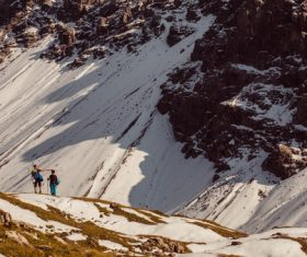 People exploring high snowy rocky mountain Stock Photo