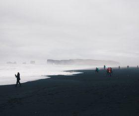People gathering on wavy cold seaside Stock Photo