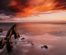 Rocky calm beach scenery at dusk Stock Photo
