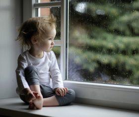 Sitting on the windowsill lonely children Stock Photo